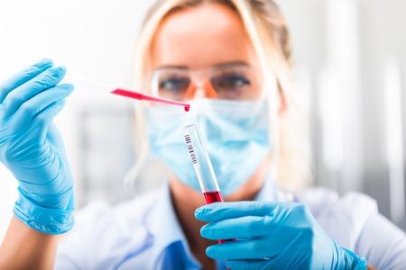 Jonge aantrekkelijke geconcentreerde vrouwelijke wetenschapper in beschermende bril, masker en handschoenen die een rode vloeistof in de proefbuis laten vallen met een pipet in het wetenschappelijk chemisch laboratorium