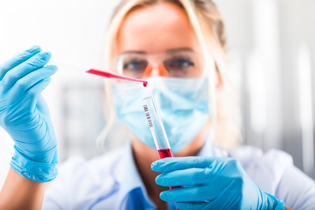 Young attractive concentrated female scientist in protective eyeglasses, mask and gloves dropping a red liquid substance into the test tube with a pipette in the scientific chemical laboratory Zdjęcie Seryjne