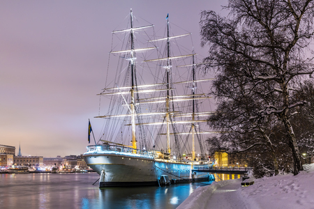 Scenic winter night view of the Old Town (Gamla Stan) with historical tall sailing ship AF Chapman at Skeppsholmen Island in Stockholm, Sweden Banco de Imagens