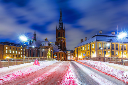Night winter scenery of the snowy street in the Riddarholmen district of the Old Town (Gamla Stan) in Stockholm, Sweden