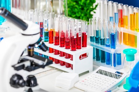 Creative abstract chemistry development, medicine, pharmacy, biology, biochemistry and research technology concept: table with scientific chemical laboratory equipment - microscope, test tubes with color liquid substance samples, vials, flasks, report documents etc. with selective focus effect
