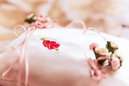 Macro view of the white decorated pillow with red heart shapes for wedding rings with selective focus effect