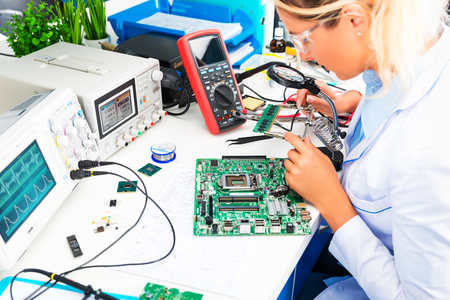 Young attractive female digital electronic engineer checking green circuit board PCB in laboratory