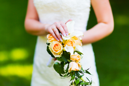 Macro view of the young bride wearing white wedding dress holding marriage flowers outdoors Stock Photo