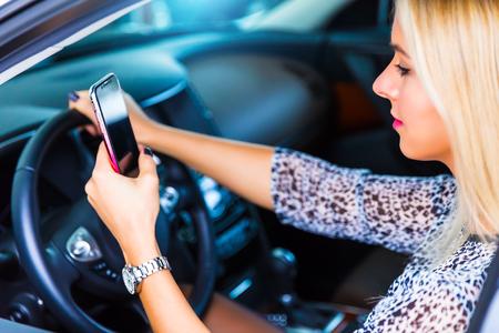 Afgeleide jonge bedrijfsvrouwenbestuurder gebruikend een smartphone en texting terwijl het drijven van een auto op een weg