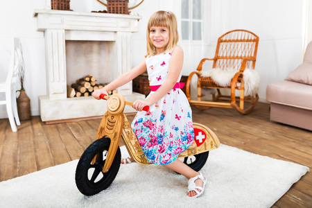 Happy smiling little girl riding a wooden runbike at home in the living room Stock Photo