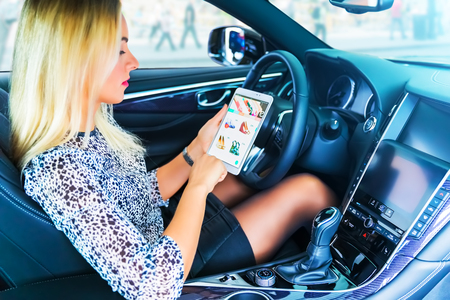 Young blond business woman driver using a tablet computer PC in the modern luxury car Stock Photo