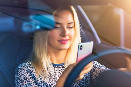 Young smiling woman driver using a smartphone in the modern luxury car