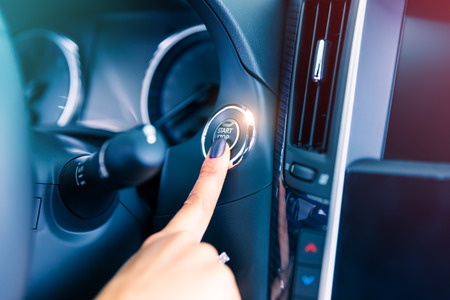 Woman driver pushing a start ignition button switch in the modern luxury car Foto de archivo