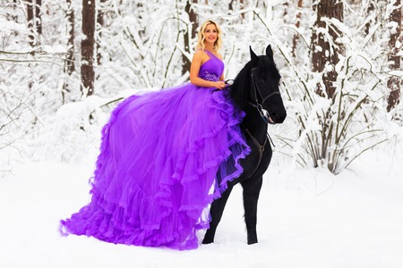 Young beautiful blonde woman wearing a long pink dress riding a black horse in the snowy winter forest
