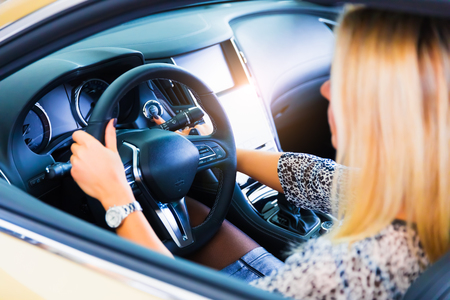 Young woman driving a modern luxury car