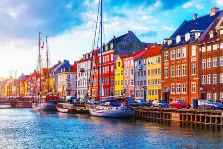 De toneelmening van de de zomerzonsondergang van Nyhavn-pijler met kleurengebouwen, schepen, jachten en andere boten in de Oude Stad van Kopenhagen, Denemarken