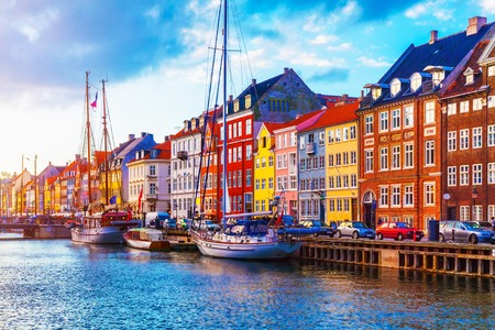Scenic summer sunset view of Nyhavn pier with color buildings, ships, yachts and other boats in the Old Town of Copenhagen, Denmark Фото со стока