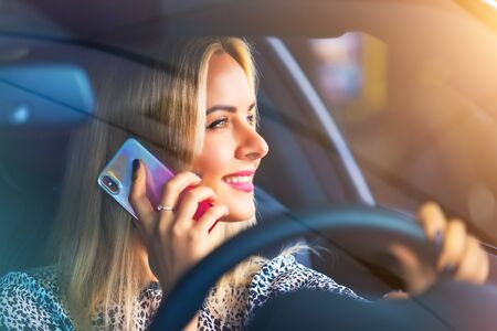 Young happy smiling woman driver talking by phone in the modern luxury car Imagens