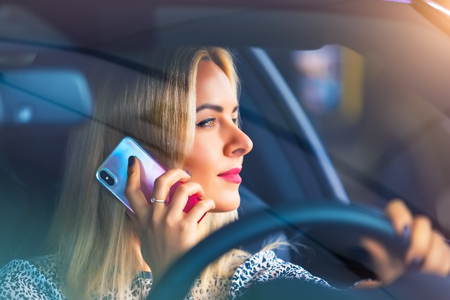Young woman driver talking by phone in the modern luxury car