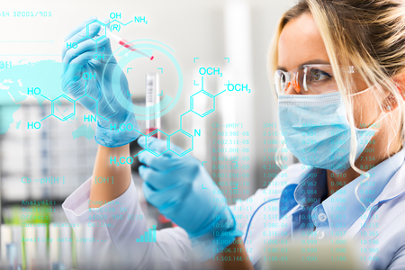 Young attractive female scientist researching in the laboratory with futuristic scientific air interface with chemical formulas and research data in the foreground