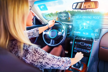 Young woman traveling in self driving autopilot car or auto