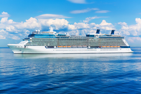 Big cruise liner ship in the blue sea or ocean with clouds