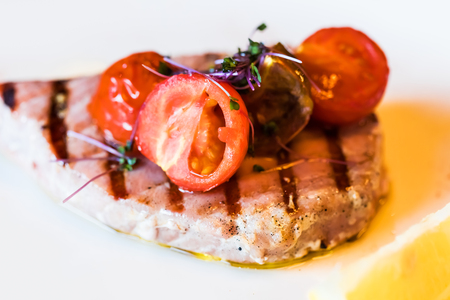 Macro view of the piece of grilled tuna fish with tomato slices and seasonings Stock Photo