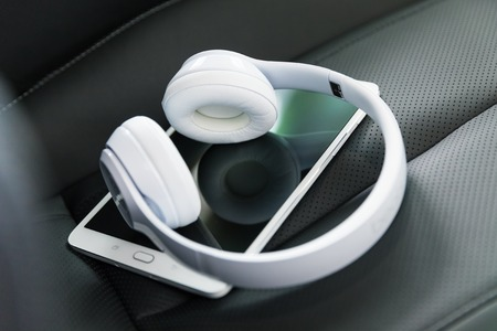 Modern wireless internet technology concept: macro view of tablet computer PC and white wireless headphones on the black leather car seat with selective focus effect Stock Photo