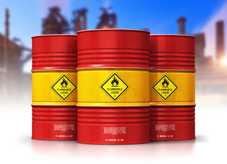 Creative abstract oil and gas industry manufacturing and trading business concept: 3D render illustration of the group of red metal oil drums or petroleum barrels in front of refinery plant isolated on white background with reflection effect Banco de Imagens