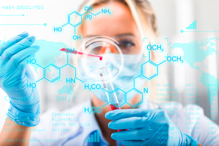 Young attractive female scientist researching in the laboratory with futuristic scientific air interface with chemical formulas and research data in the foreground Stock Photo