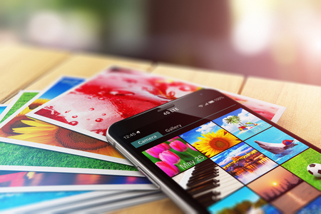 Creative abstract 3D render illustration of the macro view of stack of color photo pictures and smartphone with image gallery app on the screen on wooden table outdoors with selective focus bokeh blur effect
