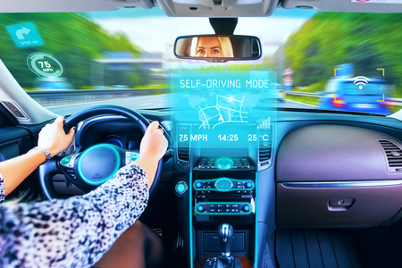 Young woman traveling in self driving  mode autopilot business luxury car or auto on the highway or autobahn with motion blur effect