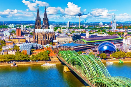 Scenic summer aerial panorama of the Old Town pier architecture with Cathedral Church and Hohenzollern railway bridge over Rhine River in Cologne or Koln, North Rhine-Westphalia, Germany