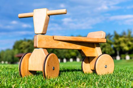 Wooden children runbike on the green grass field in the garden or park nature outdoors