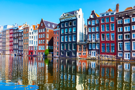 Scenic summer view of iconic ancient medieval buildings and canal pier architecture in the Old Town of Amsterdam, Netherlands