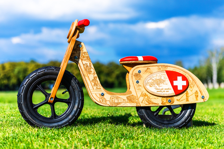 Wooden children runbike on the green grass field in the garden or park nature outdoors