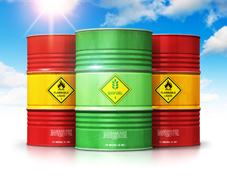 Creative abstract ecology, alternative sustainable energy and environment protection saving business concept: 3D render illustration of green biofuel or biodiesel barrel in front of the group of red metal oil, petroleum or gas drums against blue sky with clouds and sun light isolated on white background with reflection effect Stockfoto