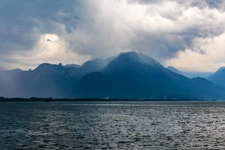 Bad cloudy overcast dramatic weather - storm, wind and rain on Geneva lake, Alps Moutains, Switzerland 스톡 콘텐츠