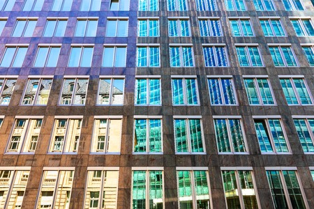 Creative abstract architectural style contrast background: old house and modern high skyscraper building reflect in glass mirror windows in the city street Stockfoto