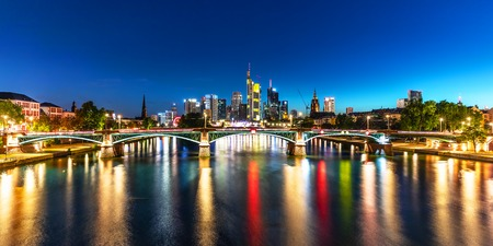 Scenic summer night panorama of the business corporate downtown bank district with high tall skyscraper buildings and illuminated bridge over the Main River in Frankfurt am Main, Germany Stockfoto