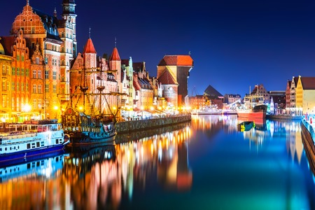 Scenic night view of the Old Town pier architecture of Gdansk, Poland at the Motlawa River harbor embankment with medieval port crane and historical ships