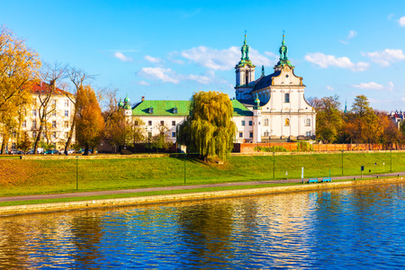 Scenic autumn view of ancient Christian Church at the Vistula river embankment in the Old Town of Krakow, Poland