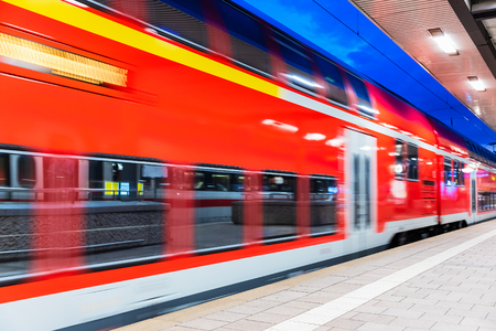 Creative abstract railroad travel and railway transportation industrial concept: modern red high speed electric passenger commuter double deck train at the illuminated station platform at night with motion blur effect Stockfoto