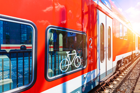 Creative abstract railroad travel and railway transportation industrial concept: modern red high speed electric passenger commuter double deck train with bicycle symbol or sign at the station platform