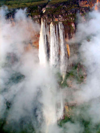 cascade: Angel Falls in Venezuela, from a planes point of view peeking through the clouds. Stock Photo