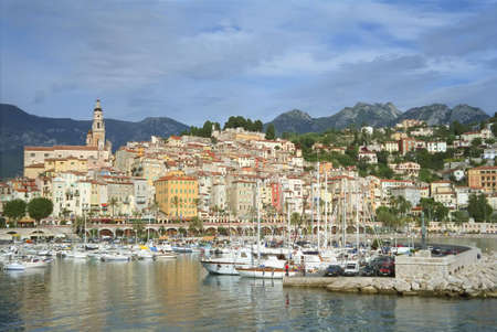 menton: Harbor view of Menton, France old town with the Alps in the background.
