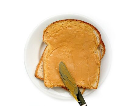 Peanut butter being spread onto a slice of bread.