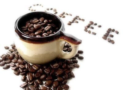 A mug filled with coffee beans, the word