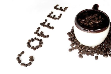 A mug filled with coffee beans, the word coffee spelled out in beans next to it.