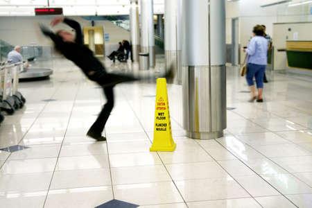 El hombre se desliza al lado de signo piso húmedo  Foto de archivo