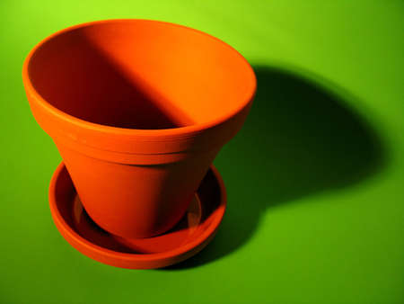 An orange clay flower pot with deep shadows on a bright green background. Stock fotó