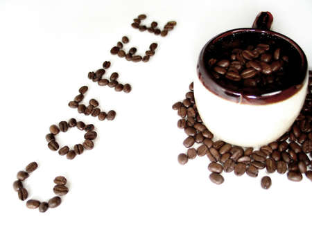 A mug filled with coffee beans, the word coffee spelled out in beans next to it. Banco de Imagens