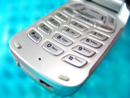 Closeup of cellphone buttons upon a blurred aqua background Stock Photo