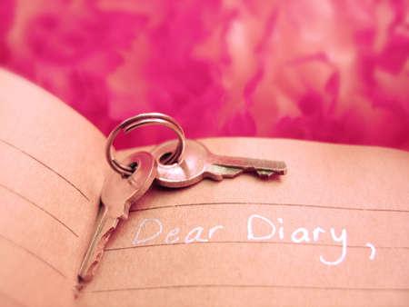 sleutels bovenop een dagboek met een roze achtergrond
